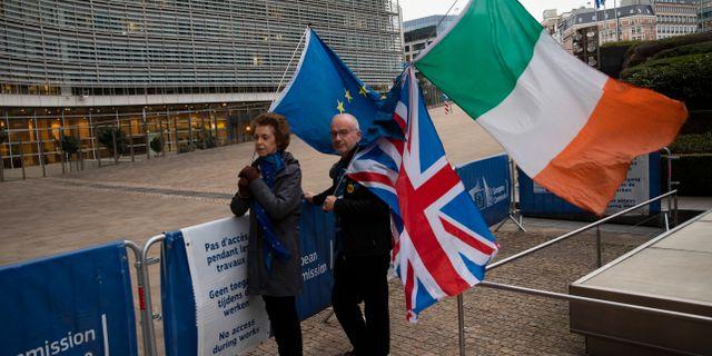 Ett par står med Storbritanniens, Irlands och EU:s flaggor utanför EU-kommissionen i Bryssel.  Francisco Seco / TT NYHETSBYRÅN