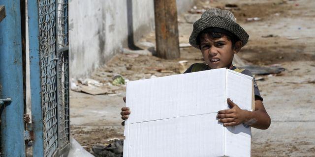 En palestinsk pojke bär på ett matpaket.  SAID KHATIB / AFP
