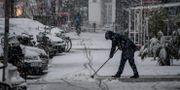 En kvinna sopar bort snö i Hamburg.  AXEL HEIMKEN / dpa