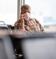 Man med munskydd på flygplats. Illustrationsbild. Mikael Fritzon/TT / TT NYHETSBYRÅN