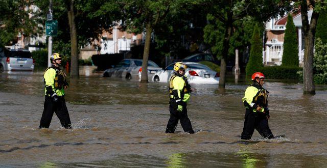 Brandmän i Philadelphia går genom översvämmat område.  Matt Slocum / TT NYHETSBYRÅN