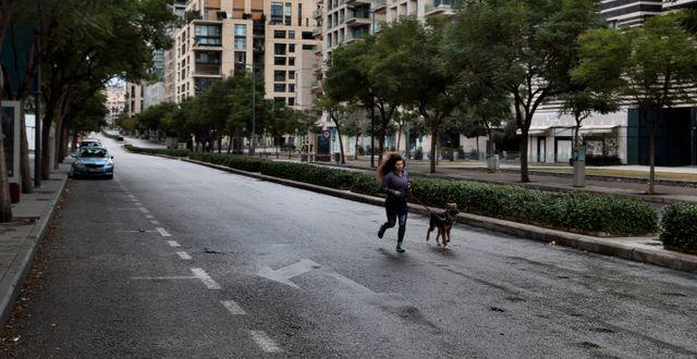 Kvinna joggar med sin hund i ett i övrigt folktomt Beirut på torsdagen. Bilal Hussein / TT NYHETSBYRÅN
