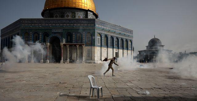Palestinsk man flyr från tårgas under sammandrabbningar med israelisk polis framför Klippdomen i Jerusalem. Mahmoud Illean / TT NYHETSBYRÅN