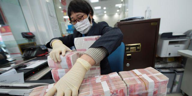 Illustrationsbild: En anställd vid en bank i Nantong, Jiangsu-provinsen, sorterar yuan-sedlar.  CHINA DAILY / TT NYHETSBYRÅN