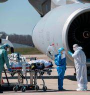 Sjukvårdspersonal i Grand Est flyttar coronasjuka patienter. SEBASTIEN BOZON / TT NYHETSBYRÅN