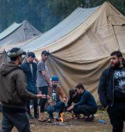 Migranter lagar mat i ett flyktingläger 38 kilometer söder om Vilnius, 6 augusti, 2021.  Mindaugas Kulbis / TT NYHETSBYRÅN