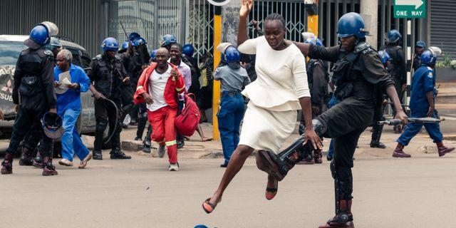 En polisman i Harare sparkar en demonstrant. JEKESAI NJIKIZANA / AFP