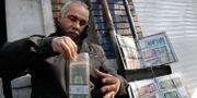 En valutaväxlare stoppar amerikanska dollar i en plastpåse i Teheran, Iran. Illustrationsbild.  Vahid Salemi / TT NYHETSBYRÅN