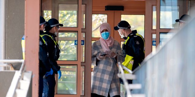 Polis talar med en kvinna i ett lägenhetskomplex i Melbourne Andy Brownbill / TT NYHETSBYRÅN