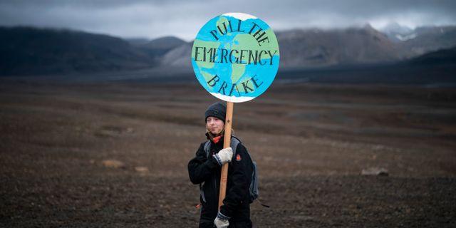 En flicka håller ett plakat med orden: Dra i nödbromsen.  Felipe Dana / TT NYHETSBYRÅN/ NTB Scanpix