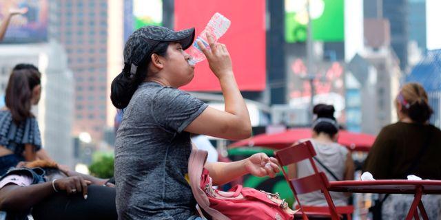 En kvinna dricker vatten på ett varmt Times Square i New York. Jonathan Carroll / TT NYHETSBYRÅN/ NTB Scanpix