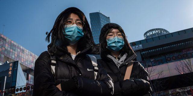 Människor i Peking bär ansiktsmasker för att skydda sig. NICOLAS ASFOURI / AFP