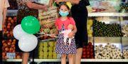 En flicka med ansiktsmask besöker en marknad i Rumänien i början av juli. Vadim Ghirda / TT NYHETSBYRÅN