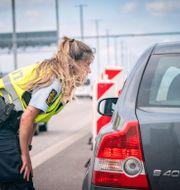 En dansk polis kontrollerar en svenskregistrerad bil på Pepparholm mellan Sverige och Danmark. Johan Nilsson/TT / TT NYHETSBYRÅN
