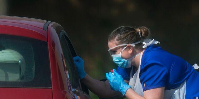En NHS-medarbetare testar en bilförare för coronaviruset i Chessington. Aaron Chown / TT NYHETSBYRÅN