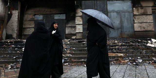 Kvinnor går förbi en byggnad som skadats under protesterna i staden Shahriar i Iran.  Vahid Salemi / TT NYHETSBYRÅN