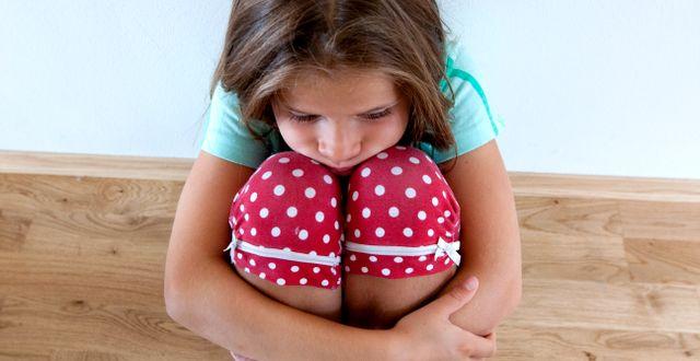 En flicka håller om sina knän/arkivbild.  Kallestad, Gorm / TT NYHETSBYRÅN