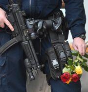 Beväpnad polis i Stockholm med blommor i handen. Fredrik Sandberg/TT / TT NYHETSBYRÅN