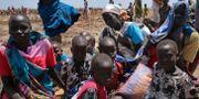 En familj i Sydsudan väntar på en mattransport. George Fominyen / TT / NTB Scanpix