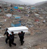 Begravningsplatsarbetare bär kvarlevorna av en man som dött i covid-19. Martin Mejia / TT NYHETSBYRÅN