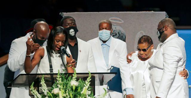 Floyds syskonbarn Brooke Williams talar på begravningen. Hon omfamnas av resten av hans familj.  Godofredo A. Vásquez / TT NYHETSBYRÅN