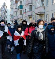 Demonstranter med oppositionens rödvita flagga. TT NYHETSBYRÅN