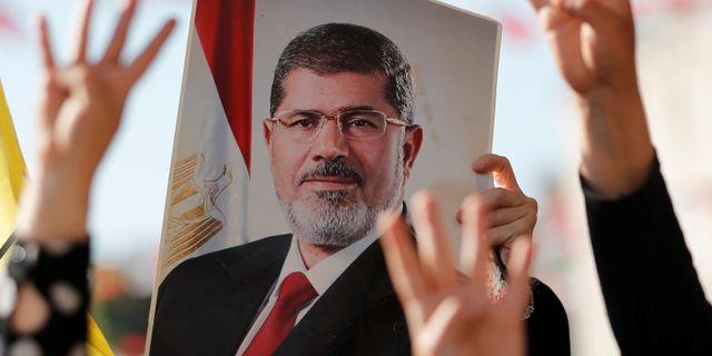 Folksamling håller upp porträtt av Muhammad Mursi.  MURAD SEZER / TT NYHETSBYRÅN