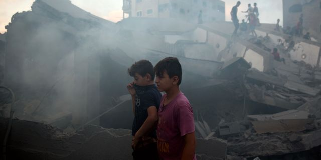 Palestinier granskar skadorna på en byggnad efter Israels flygräd mot Gaza City 9 augusti.  Khalil Hamra / TT NYHETSBYRÅN