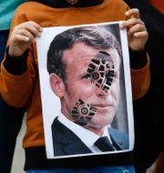 En pojke i Istanbul håller upp en nidbild på Macron under en demonstration förra söndagen. Emrah Gurel / TT NYHETSBYRÅN