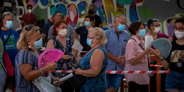 Människor med munskydd i Barcelona. Emilio Morenatti / TT NYHETSBYRÅN