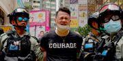 En demonstrant har pepparsprejats och förs bort av polis. Vincent Yu / TT NYHETSBYRÅN