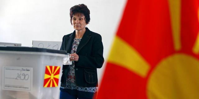 En kvinna lägger sin röst i en vallokal i Skopje. OGNEN TEOFILOVSKI / TT NYHETSBYRÅN