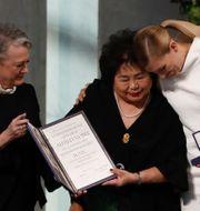 Beatrice Fihn och Hiroshima-överlevaren Setsuka Thurlow tar emot fredspriset från Berit Reiss Andersen, ordförande i fredspriskommittén.  ODD ANDERSEN / AFP