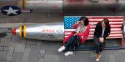 Två kvinnor i Peking vilar på en bänk utanför ett varuhus.  Ng Han Guan / TT / NTB Scanpix