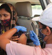 En kvinna vaccineras i sin bil i Ahmedabad.  Ajit Solanki / TT NYHETSBYRÅN
