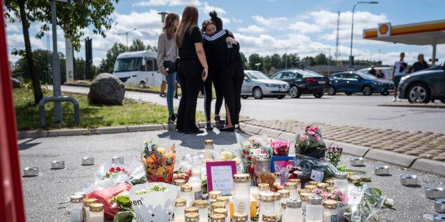 Blommor och ljus på platsen där en 12-årig flicka sköts ihjäl vid en bensinmack i Hallunda i Botkyrka, söder om Stockholm natten mot söndagen. Stina Stjernkvist/TT / TT NYHETSBYRÅN