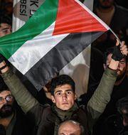En man håller en palestinsk flagga utanför USA:s konsulat i Istanbul. OZAN KOSE / AFP