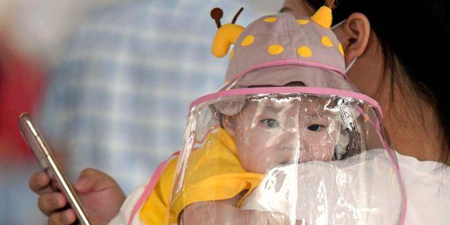 Resenär med bebis på flygplatsen i Wuhan. Naohiko Hatta / TT NYHETSBYRÅN