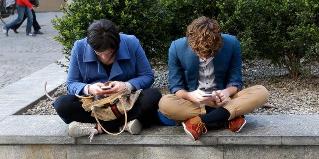 En ung man och en ung kvinna med sina mobiltelefoner i Milano, Italien. Illustrationsbild. Luca Bruno / TT NYHETSBYRÅN