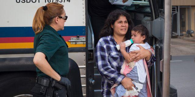 En kvinna släpps från ett förvar tillsammans med sitt barn. LOREN ELLIOTT / AFP