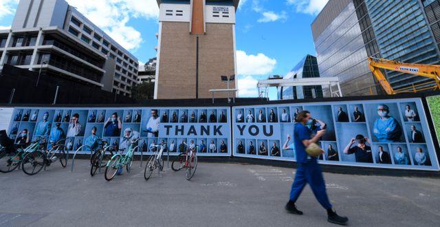 En man går förbi en fotoutställning i Melbourne där vårdpersonal tackas. James Ross / TT NYHETSBYRÅN