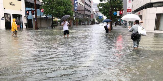 Invånare vadar fram över gatorna i staden Saga, Japan.  JIJI PRESS / JIJI PRESS