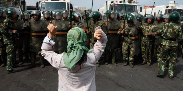 Uigurisk kvinna protesterar framför paramilitär polis i Xinjiang. Ng Han Guan / TT NYHETSBYRÅN/ NTB Scanpix
