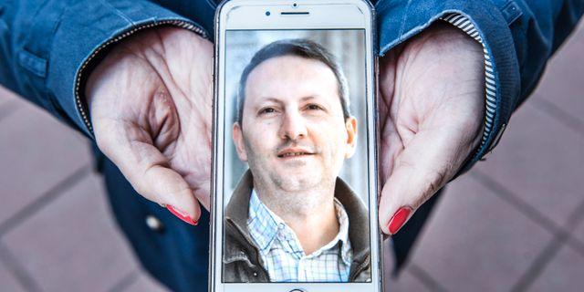 Forskarens fru Vida Mehrannia visar upp en bild av sin make i telefonen. Tomas Oneborg/SvD/TT / TT NYHETSBYRÅN