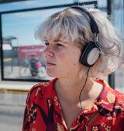 Illustration: Kvinna med hörlurar. Stina Stjernkvist/TT / TT NYHETSBYRÅN