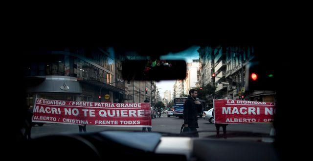 Supportrar av oppositionen som demonstrerar i Buenos Aires, sedda genom ett bilfönster.  Natacha Pisarenko / TT NYHETSBYRÅN/ NTB Scanpix