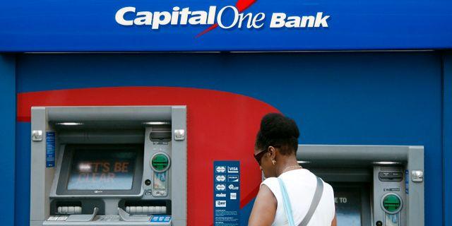 En kvinna vid en av en den drabbade banken Capital Ones bankomater.  Mark Lennihan / TT NYHETSBYRÅN