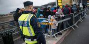 En polis övervakar kön av ankommande flyktingar i snålblåsten vid Hyllie station utanför Malmö en torsdagseftermiddagen 2015. Johan Nilsson/TT / TT NYHETSBYRÅN
