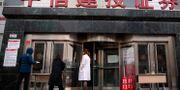 Kö utanför en aktiemäklare i Peking som bara höll öppet för begränsade transaktioner genom en lucka i dörren.  Mark Schiefelbein / TT NYHETSBYRÅN
