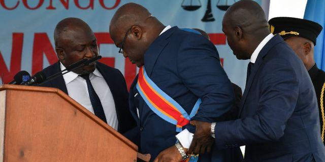 Felix Tshisekedi får hjälp av en medarbetare. TONY KARUMBA / AFP